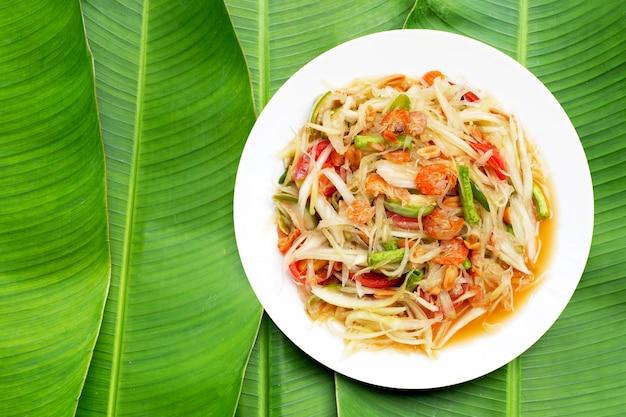 Teller mit würzigem papayasalat in weißer platte auf bananenblatthintergrund.