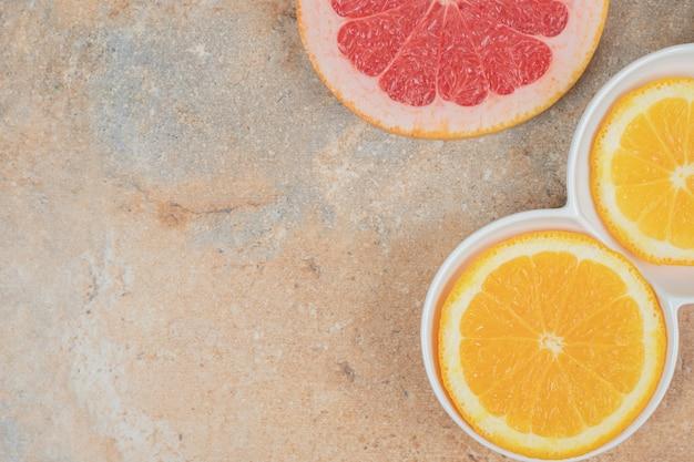 Teller mit zitronen- und grapefruitscheiben auf marmorhintergrund.