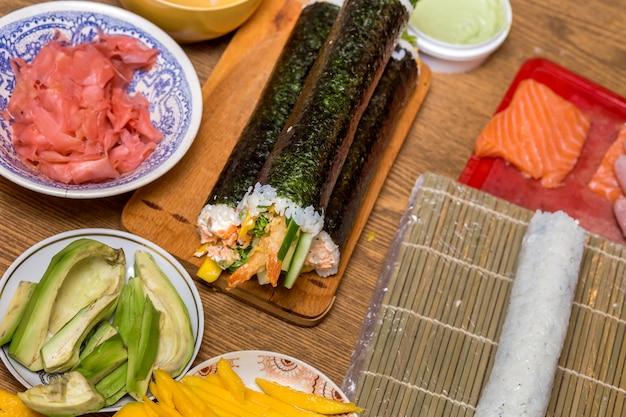 Teller mit zutaten für sushirollen auf holzbrett