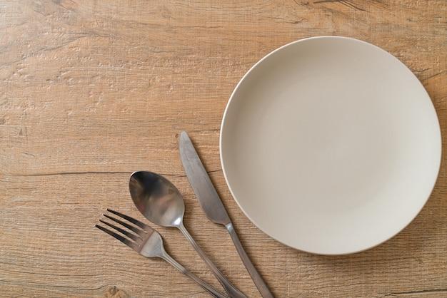 Teller oder schüssel mit messer, gabel und löffel auf holzfliesen leeren