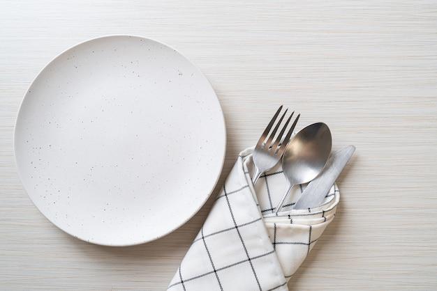 Teller oder schüssel mit messer, gabel und löffel auf holztisch leeren