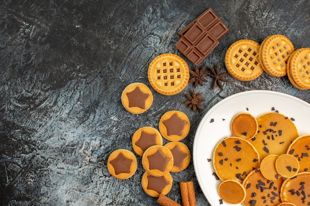 Teller pfannkuchen mit verschiedenen süßen keksen auf der rechten seite des grauen bodens