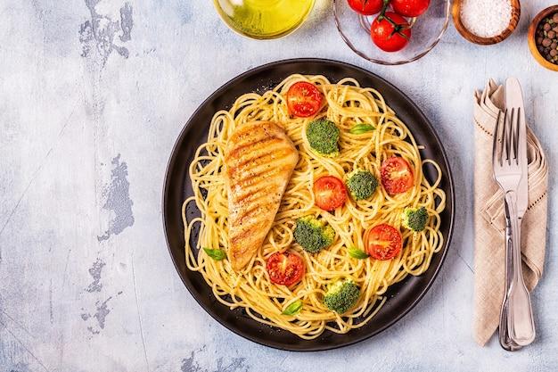 Teller spaghetti mit tomaten, brokkoli und hühnchen