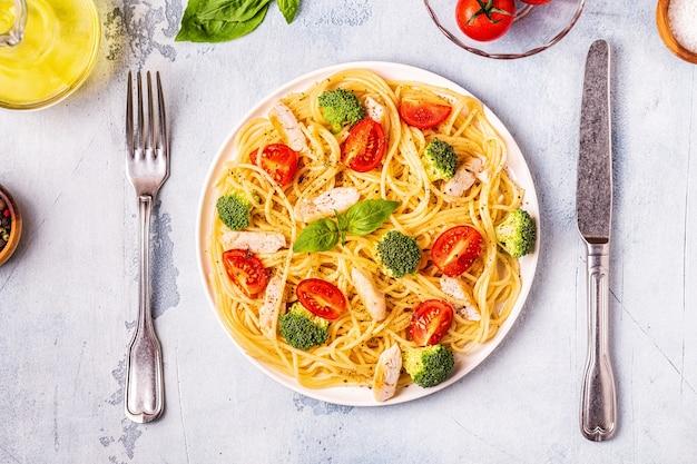 Teller spaghetti mit tomaten-, brokkoli- und hühnchenscheiben