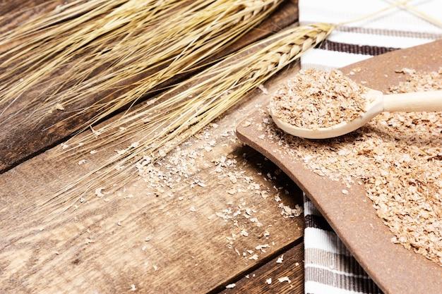 Teller und löffel gefüllte weizenkleie neben weizenähren auf holztisch konzept für gesunde ernährung