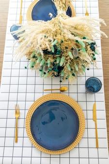 Teller und utensilien auf dem tisch, dekoriert mit einem kleinen und schönen blumenarrangement