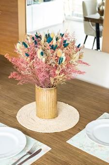 Teller und utensilien auf dem tisch mit einem kleinen blumenarrangement verziert