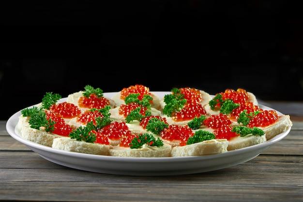 Teller voll von köstlichen roten kaviarbutter-häppchen, die auf holztisch auf schwarzem wand-copyspace serviert werden, der nahrungsmittel-delikatessen-gourmet-meny-kochendes vorspeisenkonzept isst.