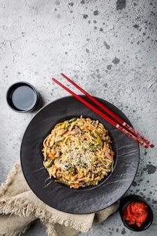 Teller wok oder bratnudeln mit fleisch und gemüse auf grauem stein