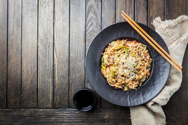Teller wok oder pfannennudeln mit fleisch und gemüse über holz