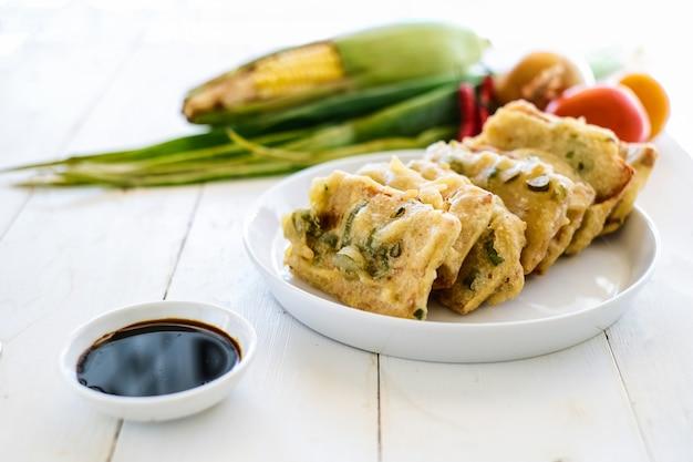 Tempe mendoan ist ein traditionelles essen aus tempeh mit mehlteig bedeckt mit einer mischung aus geschnittenem lauch und gewürzen. gekocht durch braten