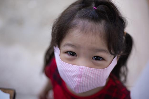 Temperaturprüfung für asiatisches mädchen in der kirche. asiatisches mädchen, das körpertemperatur misst und eine gesichtsmaske trägt.