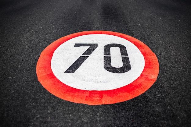 Tempolimitschild mit 70 km / h auf dunkler asphaltstraße.