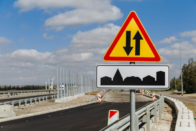 Temporäres verkehrszeichen gegenverkehr und verkehrszeichen den beginn des dorfes gegen den himmel und die im bau befindliche straße.