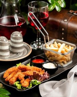 Tempura-garnelen mit pommes frites ketchup mayo und kompott auf dem tisch