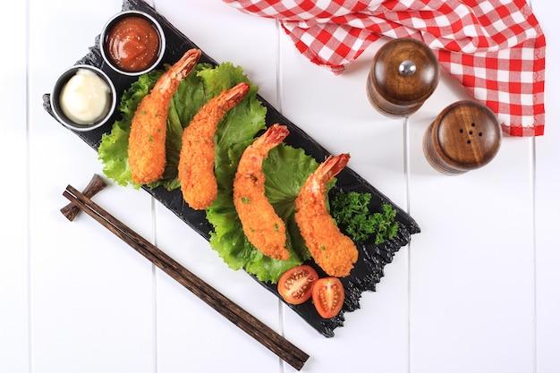 Tempura-garnelen oder garnelen oder ebi furai japanische traditionelle küche, frittierte garnelen, überzogen mit brotkrumen oder panko, normalerweise als bento-mittagsmenü zu finden. auf weißem holzhintergrund textfreiraum
