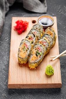 Tempura-sushi-rollen mit käse und krabbenfleisch auf dem holzbrett