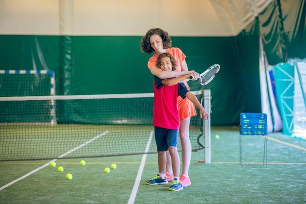 Tennis. frau in hellen kleidern, die einen jungen lehren, tennis zu spielen