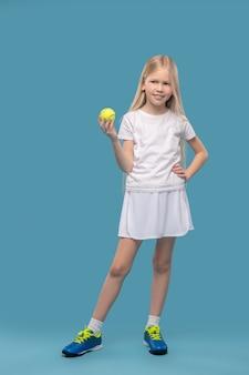 Tennis, sport. lächelndes langhaariges mädchen in weißer sportkleidung mit hellem tennisball in der hand auf blauem hintergrund