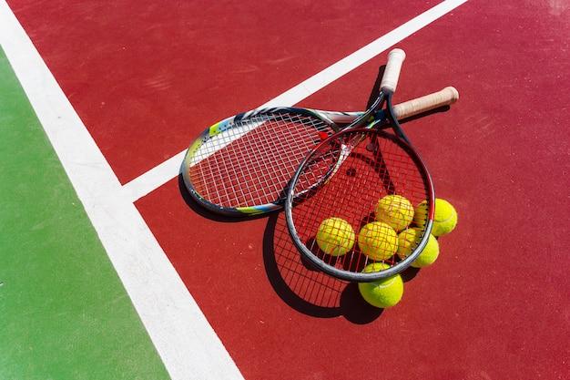 Tennisbälle und schläger auf dem rasenplatz