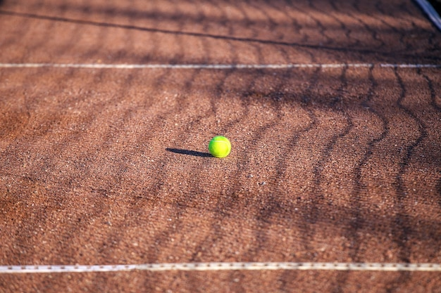 Tennisball auf einem sandplatz. sportlicher hintergrund
