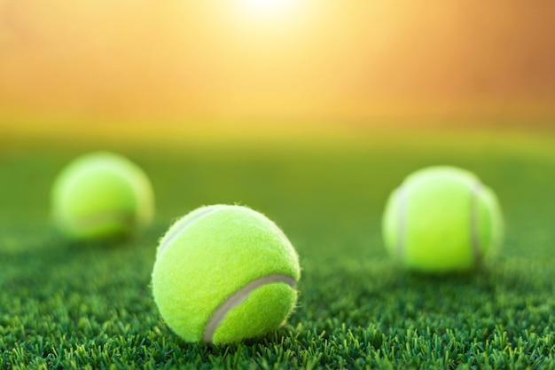 Tennisball auf gericht des grünen grases mit sonnenuntergangeffekthintergrund