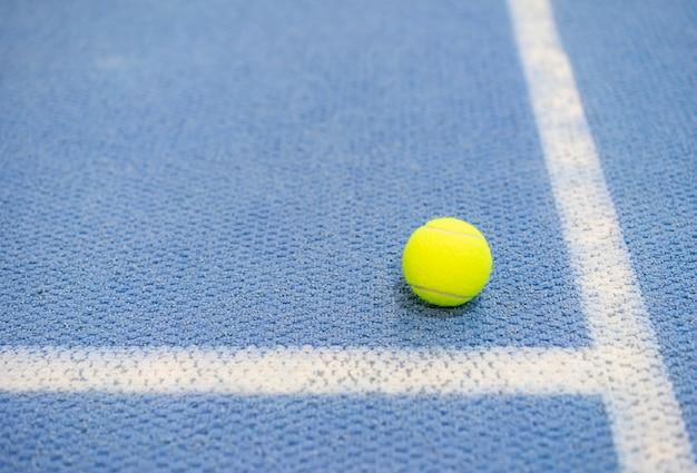 Tennisball innen auf tennisplatz, weiße linie, blaue oberfläche, kopienraum