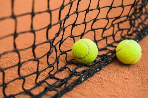 Tennisball zwei nahe dem schwarzen netz auf dem boden