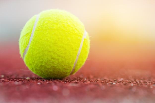 Tenniskugeln am roten gerichtsbodenhintergrund am sommertag.