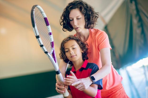 Tennislehrer. junge trainerin, die einen jungen lehrt, einen tennisschläger zu halten