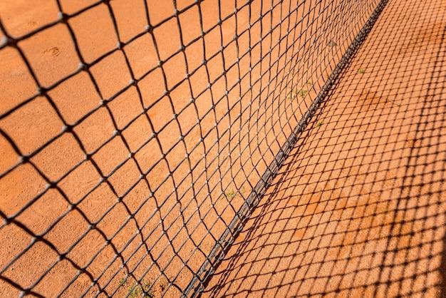 Tennisnetz auf rotem sandplatz mit linien und schatten