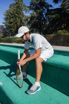 Tennisprofi, der vom tennismatch an einem sonnigen tag stillsteht