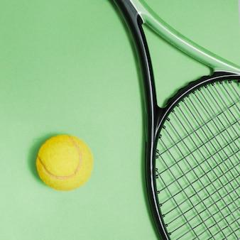 Tennisschläger, der mit gelbem ball liegt