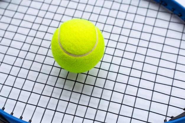 Tennisschläger mit ball auf weißer oberfläche