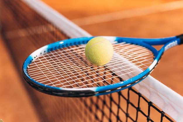 Tennisschläger mit einem ball auf dem tennisnetz
