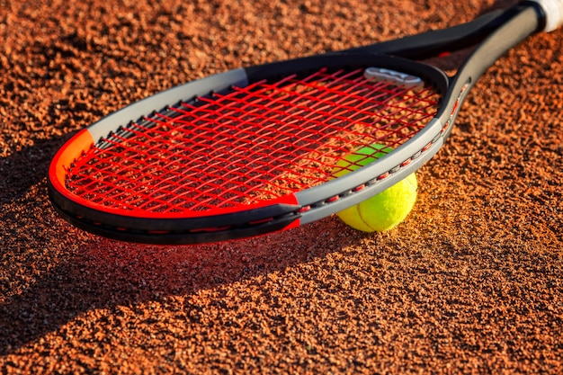 Tennisschläger mit einem ball in der nähe des netzes auf dem irdenen platz. sonniger tag. nahansicht.