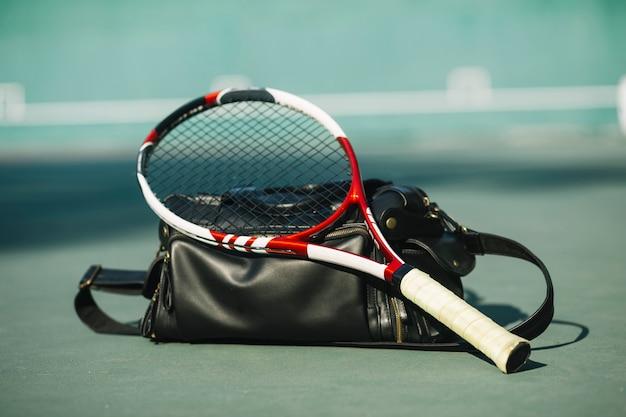 Tennisschläger mit einer tasche auf dem tennisfeld