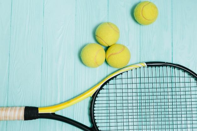 Tennisschläger mit vier gelben bällen