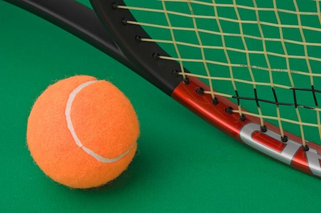 Tennisschläger und ball auf grünem hintergrund