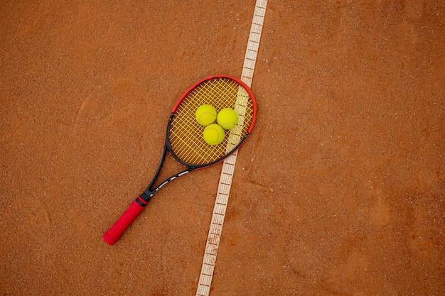 Tennisschläger und gelbe bälle auf einem ziegelroten platz.