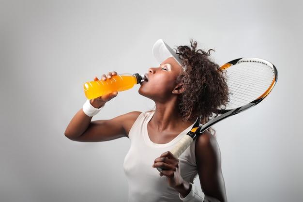 Tennisspieler, der einen saft trinkt