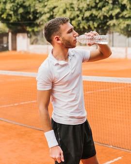 Tennisspieler, der etwas wasser trinkt