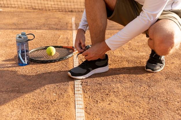 Tennisspieler, der seine schuhe bindet
