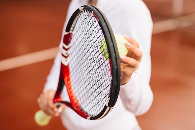 Tennisspieler, der tennisausrüstung hält