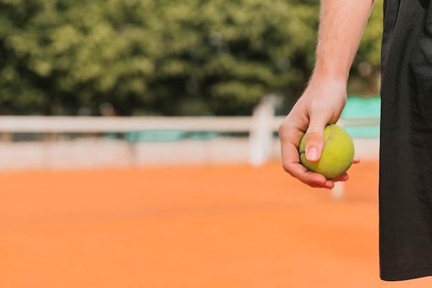 Tennisspieler, der tenniskugel anhält