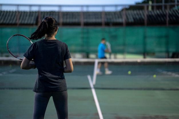 Tennisspieler, die ein match auf dem gericht an einem sonnigen tag spielen