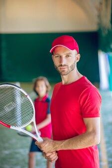 Tennisspieler. junger bärtiger mann in einer roten kappe, die mit einem tennisschläger steht