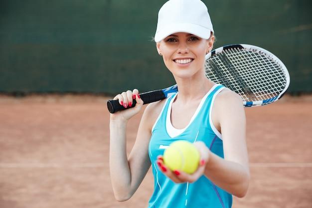 Tennisspieler mit schläger, der ball gibt