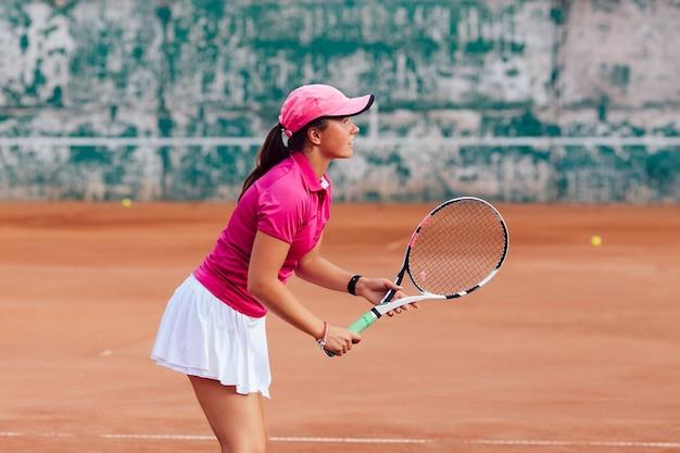 Tennisspieler. profilbild der konzentrierten frau in der sportkleidung, tennis spielend