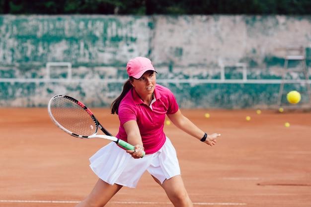 Tennisspieler. weiblicher spieler kleidete im rosa rock und in der weißen bluse an und spielte tennis auf gericht